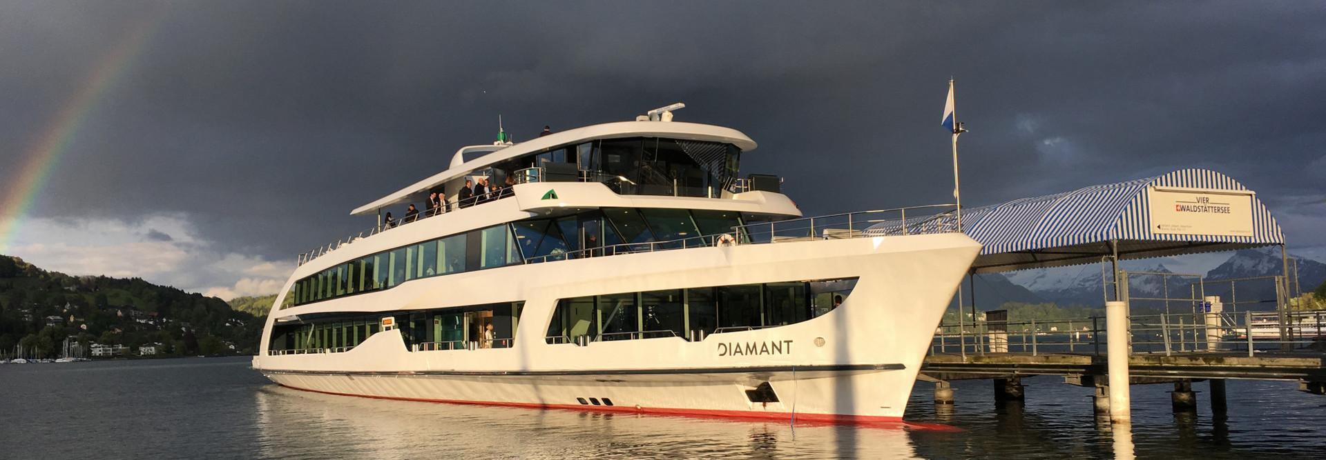 Das Motorschiff Diamant schwimmt am Steg. Im Hintergrund ist ein Regenbogen zu sehen.
