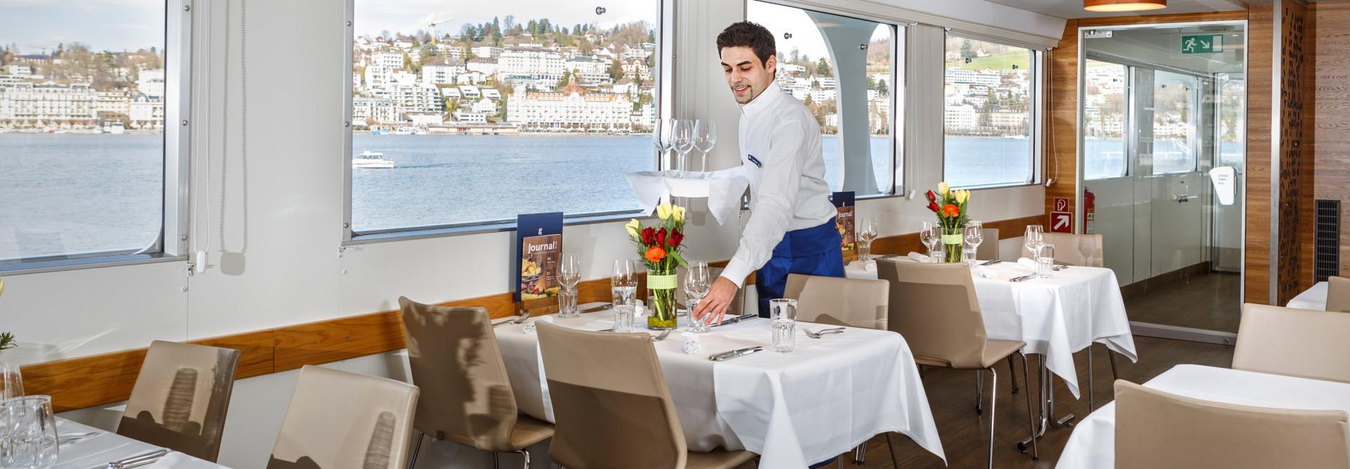Der Chef de Service deckt den Tisch auf dem Motorschiff.