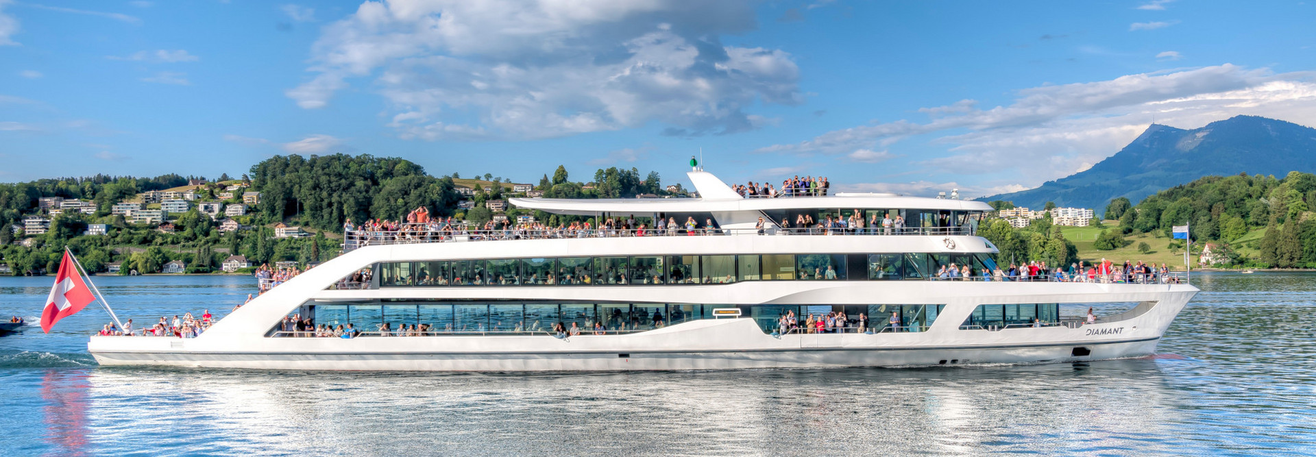 The motor ship Diamant sails on Lake Lucerne on a beautiful summer day fully loaded with happy guests.