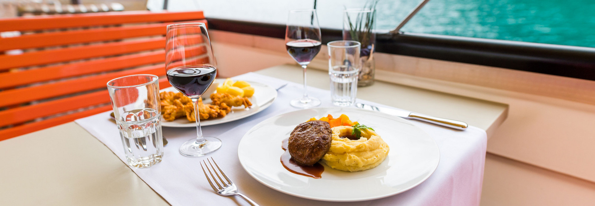 A table on a steamer is set for two people. The food is already on the table and the wine glasses are filled with red wine.