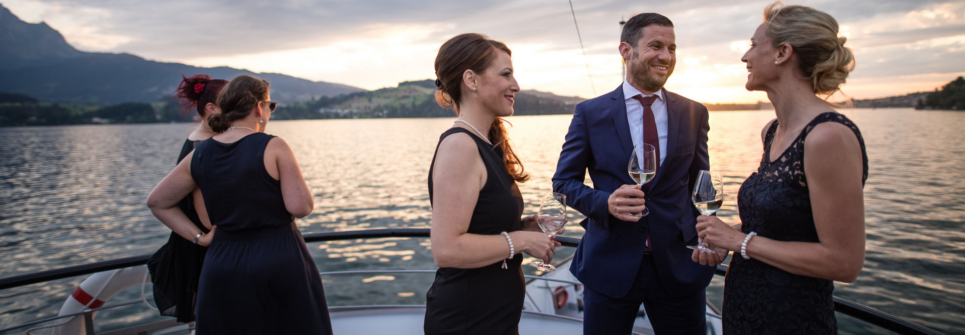 Guests of a company event during an aperitif on Lake Lucerne.