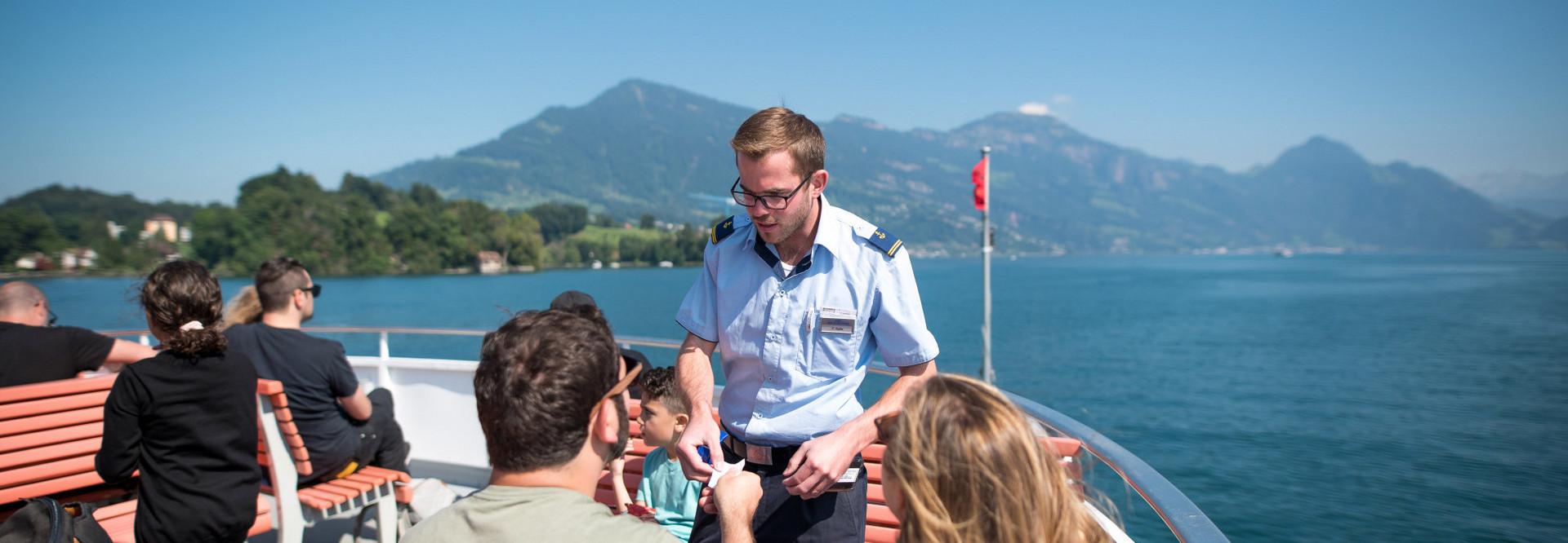 Un marin vérifie les billets de deux passagers assis à l'extérieur.