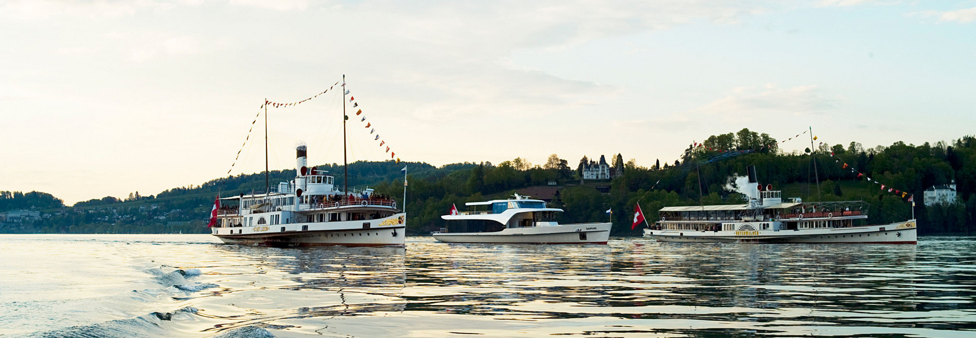 Two steamboats and a motor vessel cruise side by side on Lake Lucerne.