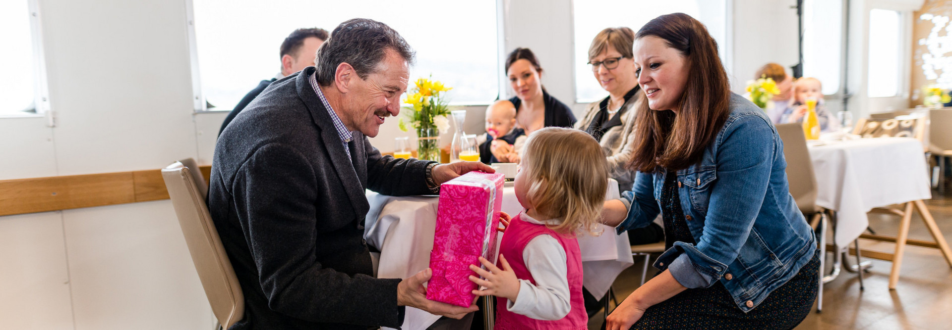 Family birthday party on the ship. A little girl gives a gift to her grandfather.