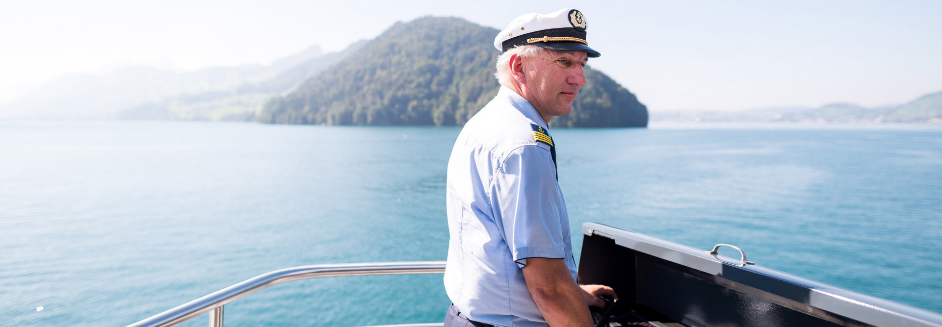 The chief captain of the SGV steers the motor vessel across Lake Lucerne.